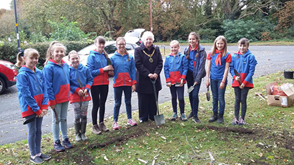 a group of girls and the mayor planting bulbs